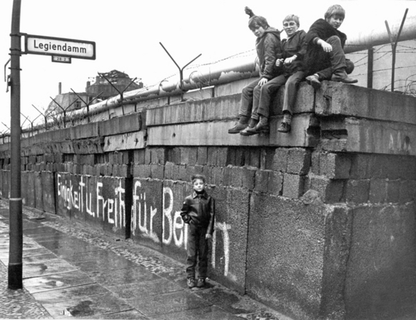 A group of children sits on the Berlin Wall at the 'Legiendamm' in the West Berlin borough Kreuzberg, March 1972. A white graffiti translates 'Unity and Freedom for Berlin'.