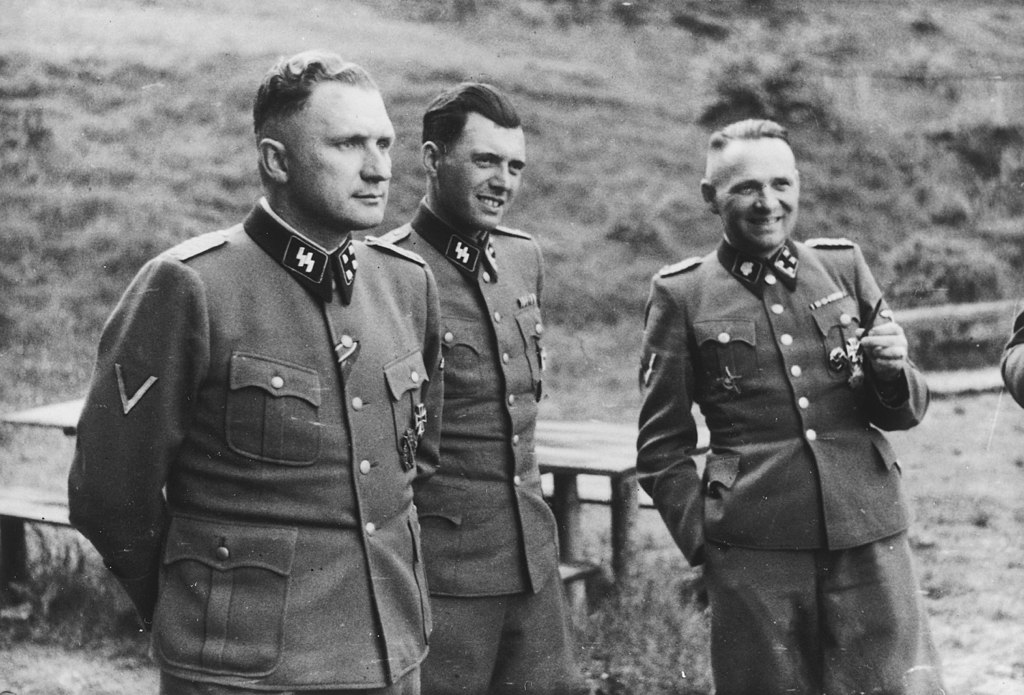 ©License: Public domain- Mengele Richard Baer, Mengele e Rudolf Höss at Auschwitz, 1944. Höcker Album